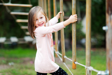 Attractive little girl on outdoor playground equipment