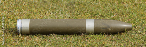 A Display Military Artillery Shell Laying on the Grass.