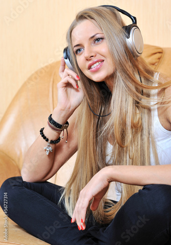 Attractive young woman listening music through headphones
