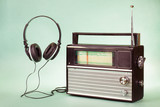 Retro radio and headphones on mint green conceptual photo