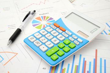 電卓とボールペンとビジネスチャート