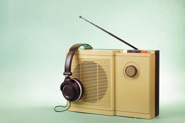 Retro radio and headphones on mint green background