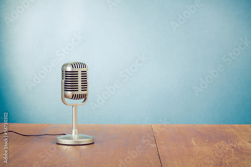 Leinwanddruck Bild Retro style microphone on table in front aquamarine background