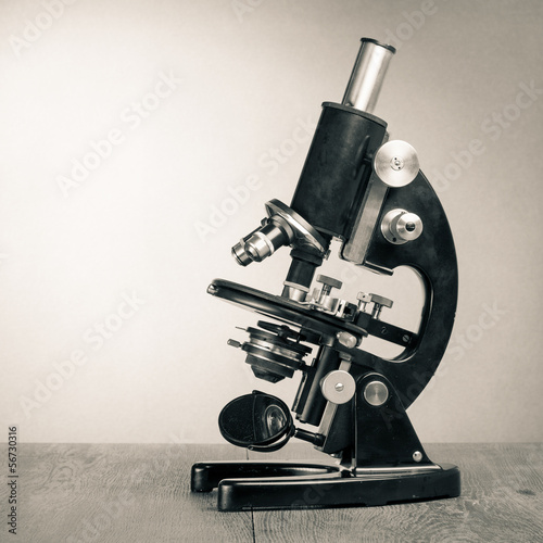 Old vintage microscope on table sepia photo