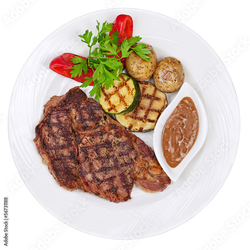Grilled steaks, baked potatoes and vegetables on white plate on