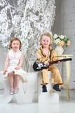 A little girl in white dress and pop musician with guitar