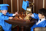 Two little boys in blue suits play chess