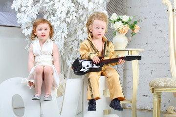 A little girl and pop musician with guitar sit on letters love