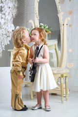 Little boy in pop retro suit kisses a girl in white dress