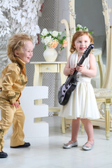 Little children in pop retro suit laugh and playing the guitar