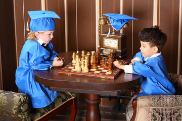 Two thoughtful boys in blue suits play chess