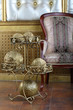 Metal stand with golden balls near chair in the interior