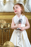 A little girl in white dress with microphone, retro style