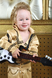 Portrait of a small boy in pop retro suit playing the guitar