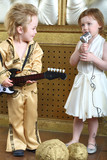 A little girl sings a song and pop musician plays guitar