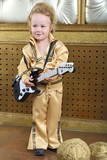 A small boy in pop retro suit playing the guitar
