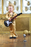 A little boy in pop retro suit playing the guitar