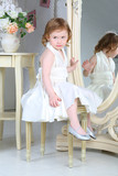 Beautiful little girl in  dress sitting in front of mirror