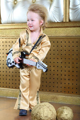 A small boy in pop retro suit with guitar