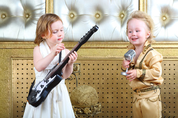 A little girl plays guitar and pop musician sings song