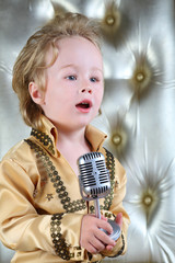 Portrait of a little boy in pop retro suit sings a song