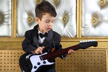A little boy in black tuxedo playing guitar