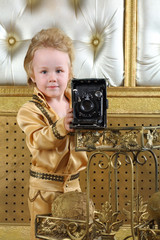 Portrait of little boy in pop retro suit with old camera