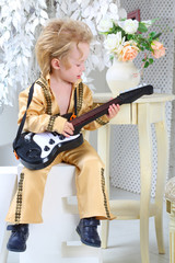 Portrait of a little boy in pop retro suit playing the guitar