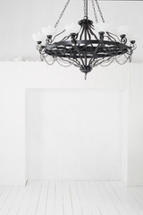 Vintage black chandelier with candles in an empty room