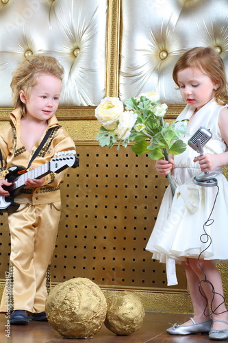 A little girl with flowers and pop musician with guitar