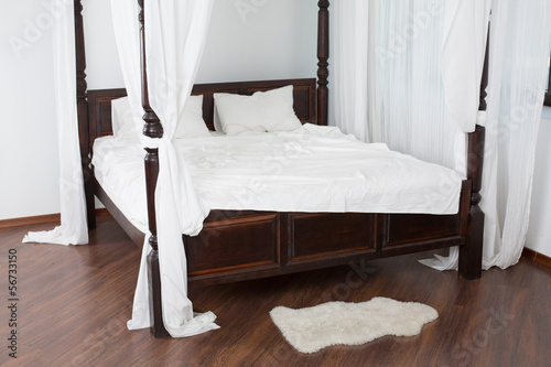 Wooden canopy bed and a white hide on the floor