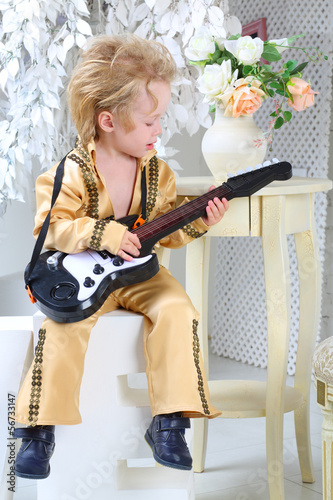 Poster Portrait of a little boy in pop retro suit playing the guitar