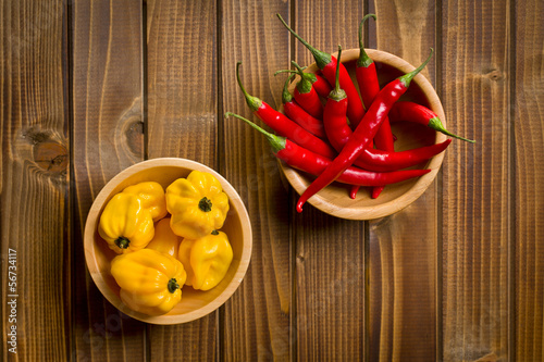 red chili peppers and habanero on wooden table