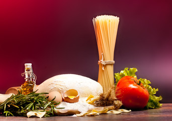 ingredients for homemade pasta on wooden table on brown backgrou