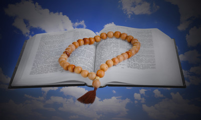 Holy Bible and wooden rosary on sky background