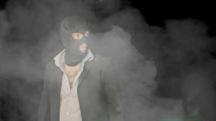 Masked criminal into smoke looking around