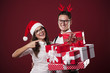 Smiling nerd couple showing christmas gifts