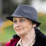 Older lady with hat and pearls smiling