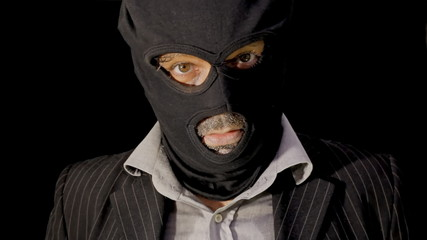Masked criminal showing up laughing close up