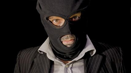 Masked criminal showing up laughing close up