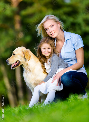 Mother and daughter with golden retriever