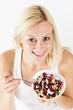 Happy blonde woman eating muesli
