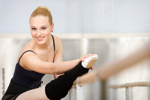 Athlete stretches herself near barre and mirrors