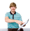 Happy young man points a finger at a blank sheet of sitting at t