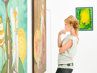 woman contemplaing colorful paintings