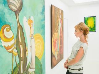 woman contemplating paintings in art gallery