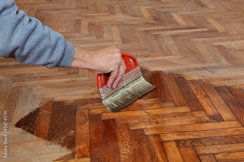 Varnishing of oak parquet floor, workers hand, brush, renovation