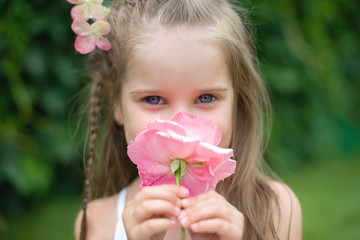 Little cute girl in garden snuff flower