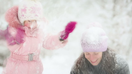 Happy woman and child playing in winter park. Slow motion