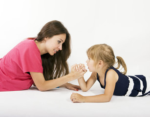 mother and daughter arm wrestling (difficult parenting)